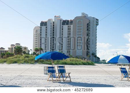 Beach With Deck Chair Near To Buildings In A Sunny Morning