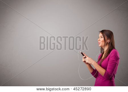 pretty young lady singing and listening to music with copy space