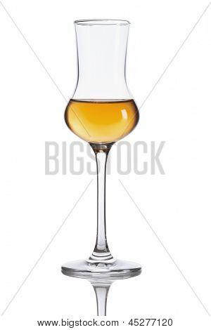 Glass of dark italian Grappa brandy isolated on white background