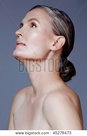 beautiful 40 year old woman with natural makeup and healthy skin texture on gray studio background