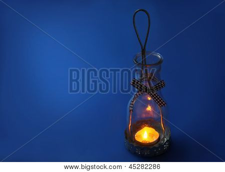 Lamp-lantern With A Candle On A Dark Blue Background