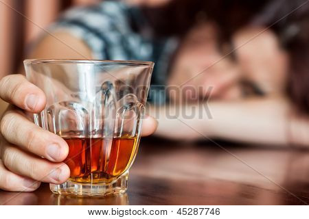 Drunk woman holding an alcoholic drink and sleeping with her head on the table (Focused on the drink, her face is out of focus)