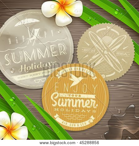 Vintage paper labels with vacation and travel emblems and tropical flowers on a wooden surface - vector illustration. (elements outside of the art-board is not cut off - they with clipping mask)
