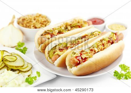 Three hot dogs with ingredients on a plate