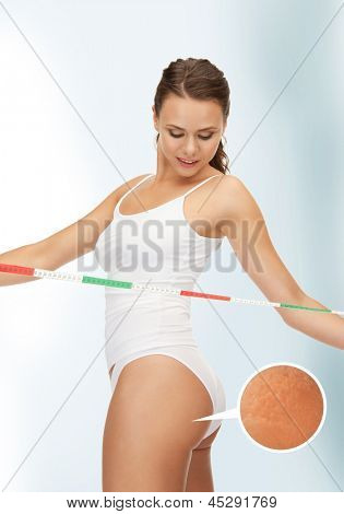 picture of woman with measuring tape looking at her cellulite