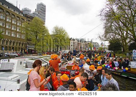 AMSTERDAM, NETHERLANDS - APRIL 30: People in orange cruising through the canals from Amsterdam during the coronation of the new king Willem Alexander from the Netherlands on 30 april 2013