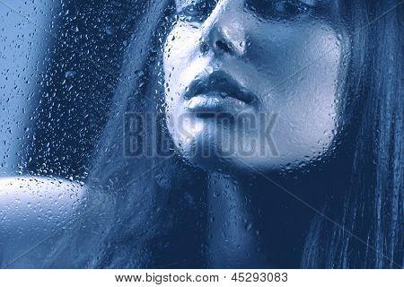 Portrait of Beauty Girl hinter dem nassen Glas. Melancholische Frau. Regen. Schönes Modell suchen Throug