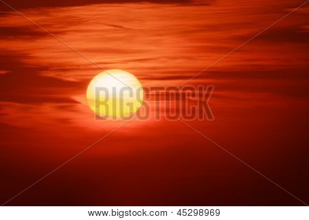 Big sun setting in clouds over red sunset sky background