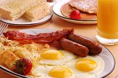 stock photo of breakfast  - A typical American hearty breakfast with sausage eggs bacon orange juice hash browns pancakes and toast - JPG