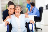 stock photo of handicapped  - caring adult daughter accompanying senior mother visiting doctor - JPG