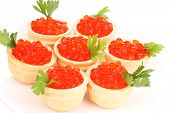 Red caviar in tartlets on white plate close-up