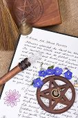 stock photo of pentacle  - wooden pentacle with incense burning with hand written book of shadows and flowers  - JPG