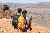 Hikers in Grand Canyon enjoying view of nature landscape. Young couple hiking relaxing during hike o