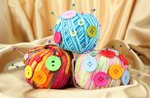 Colorful buttons and multicolor wool balls, on color fabric background