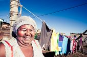 foto of curvaceous  - curvaceous african woman happily doing her washing in the townships - JPG