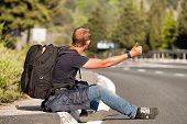 foto of wander  - Hitchhiker traveler sitting on the roadside of the mountain highway - JPG