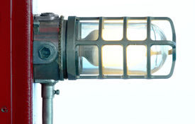 image of light fixture  - industrial looking light fixture attached to a red post - JPG