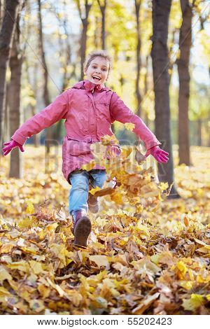 Little girl runs along autumn park and kicks up fallen leaves with her boots