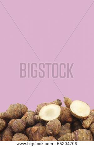 Bunch of topinambur roots (helianthus tuberosus) and a cut one on a purple background