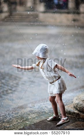 Adorable little girl outdoors on a street of old Havana checking rain