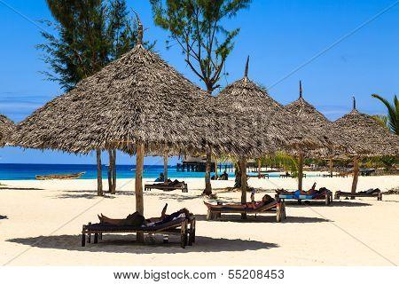 Relaxing Under An Umbrella At The Beach