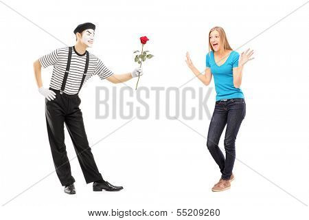 Full length portrait of a mime artist giving a rose flower to an excited woman isolated on white background