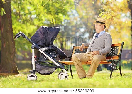 Grandfather sitting on a wooden bench and looking at his baby nephew in a stroller, in a park