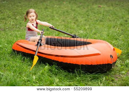 Little girl plays with a boat and oars floating on the grass