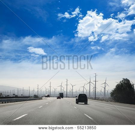 California road with electric windmills aerogenerators and traffic