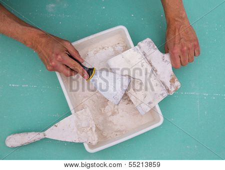 Plastering tools for plaster like plaste trowel spatula on green drywall plasterboard