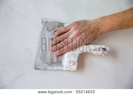Plastering man hand with plaste and plaster spatula trowel in wall