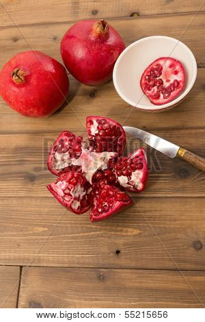 Cut open and closed pomegranates on a wooden table