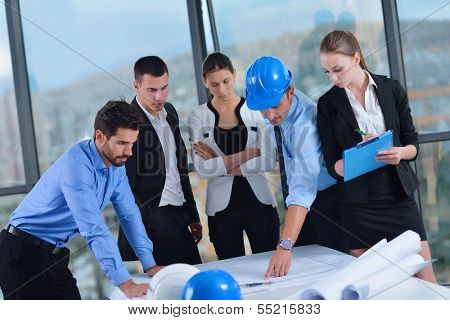 business people group on meeting and presentation  in bright modern office with construction engineer architect and worker looking building model and blueprint  plans