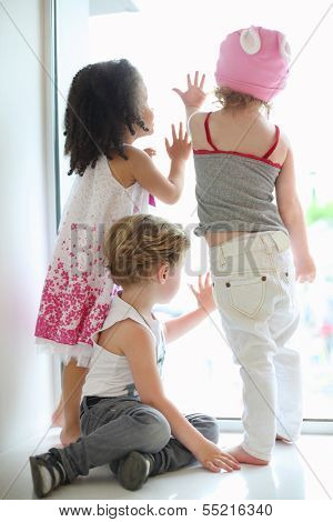 Back of three children standing near large window and looking out in big store.