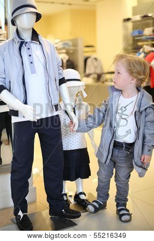 Pretty little boy holds hand of mannequin in children clothing shop.