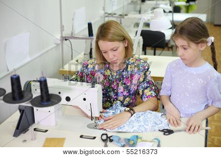 Female tailor sews at sewing machine and student girl looks at she. Focus on woman.