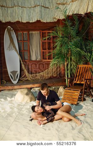 Man sits on sand and woman lies on his lap next to beach house.