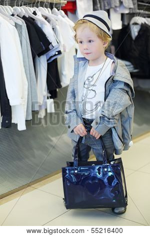 Little boy with bag stands near clothes hangers in children clothing shop.