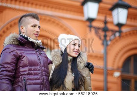 Happy man and woman look away near red building at winter day. Focus on man.