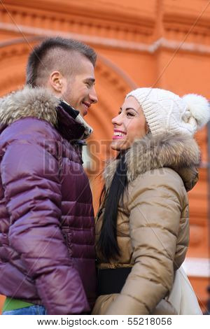 Young man and woman stand face to face and smile near red building at winter day. Focus on man.