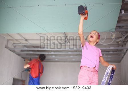 The girl with an electric screwdriver to fasten drywall on ceiling and man is working with a profile