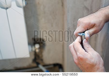 A worker cleans the pipe preparing it for crimping