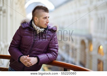 Young man in warm clothing looks away in large shopping center.