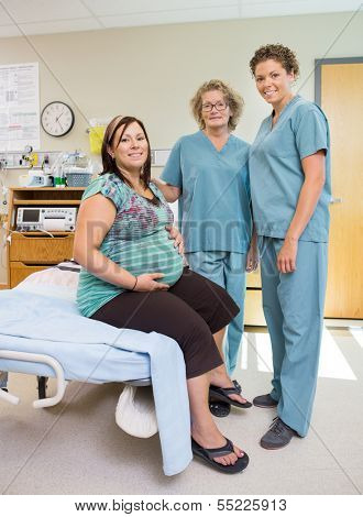 Full length portrait of happy mature female nurses with pregnant woman in hospital room
