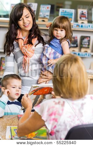 Mother and children looking at librarian showing book in library