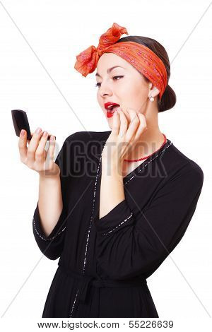 Young woman looking in the mirror and corrects make-up