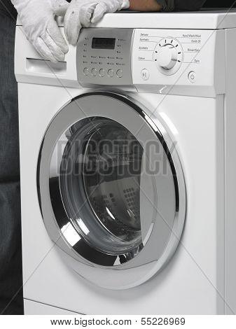 Two Hands Pushing A Washing Machine