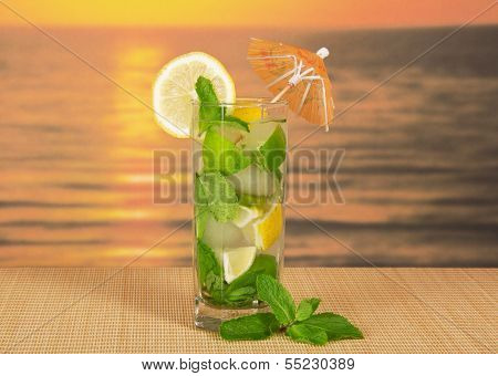 Cold drink with lemon slice against the sea sunset