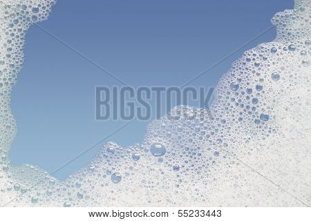 Border of bubble foam soap in blue water.