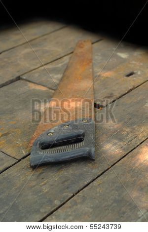 Old Rusty Saw On The Wooden Background